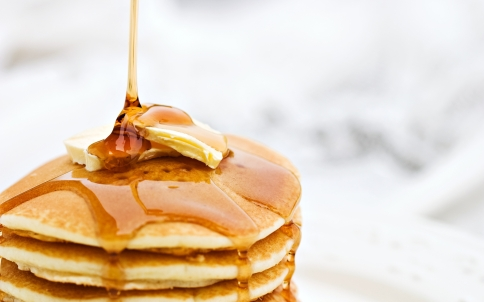 honey_being_drizzled_onto_buttered_pancakes