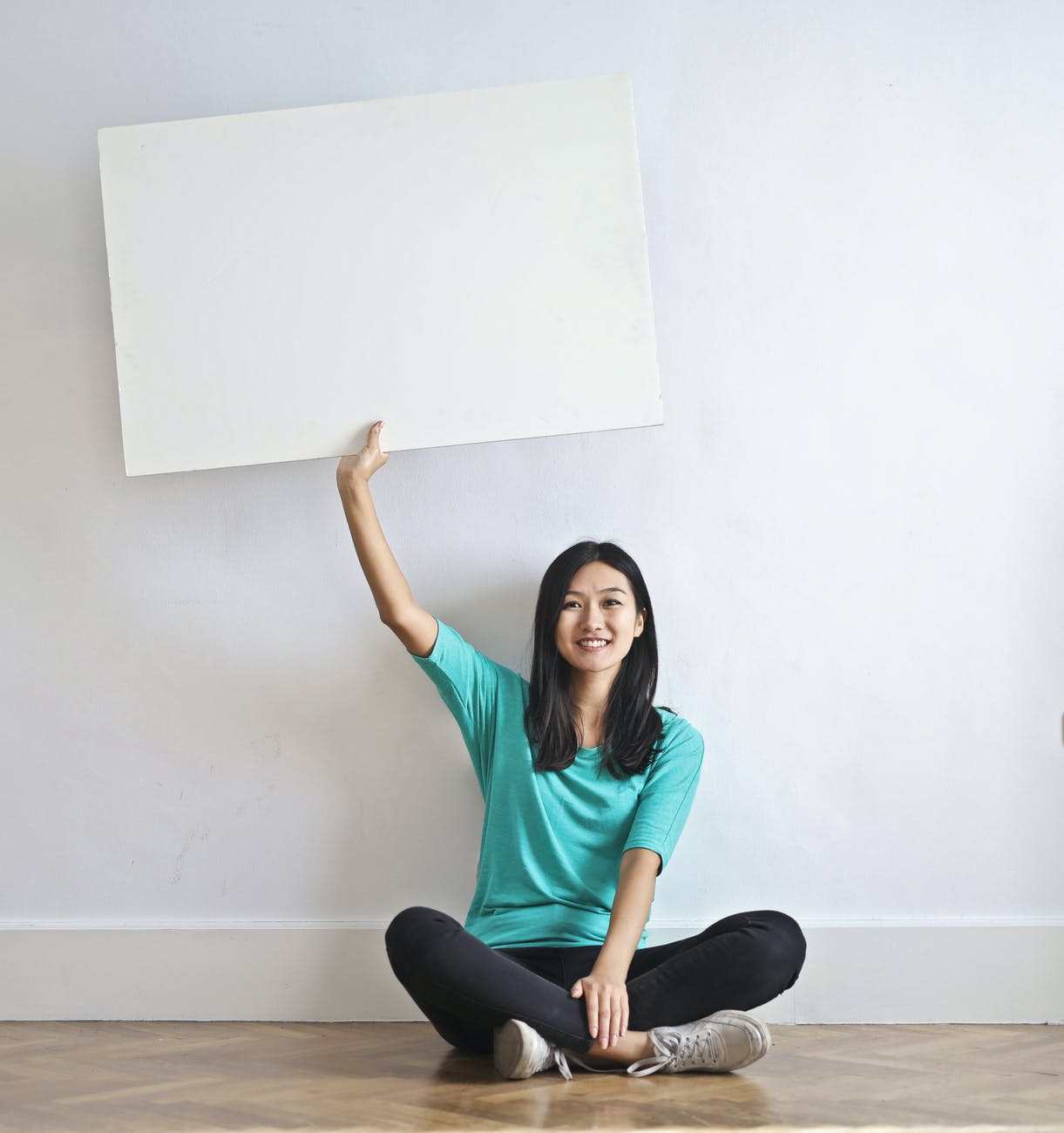 smiling ethnic woman with blank poster in empty flat